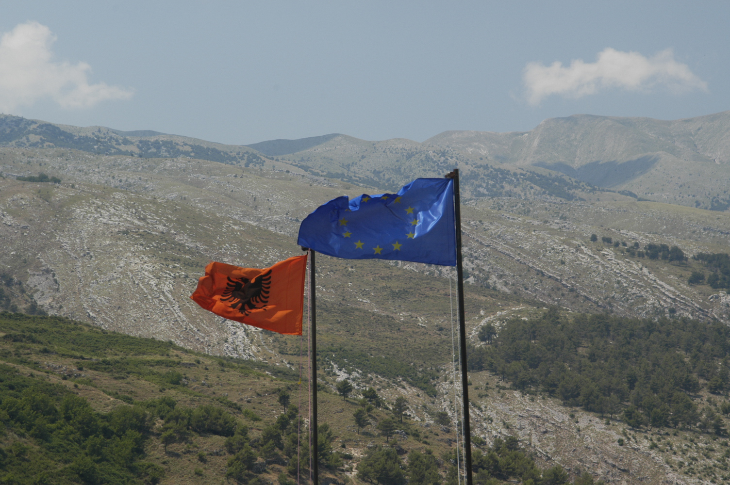The Albanian and the EU flag in front of a mountainside in Gjirokastra, Albania; SpotlightEurope_Zoela3
