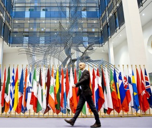 Man walking past European flags in the European Parliament, Brussels, Spotlight Europe