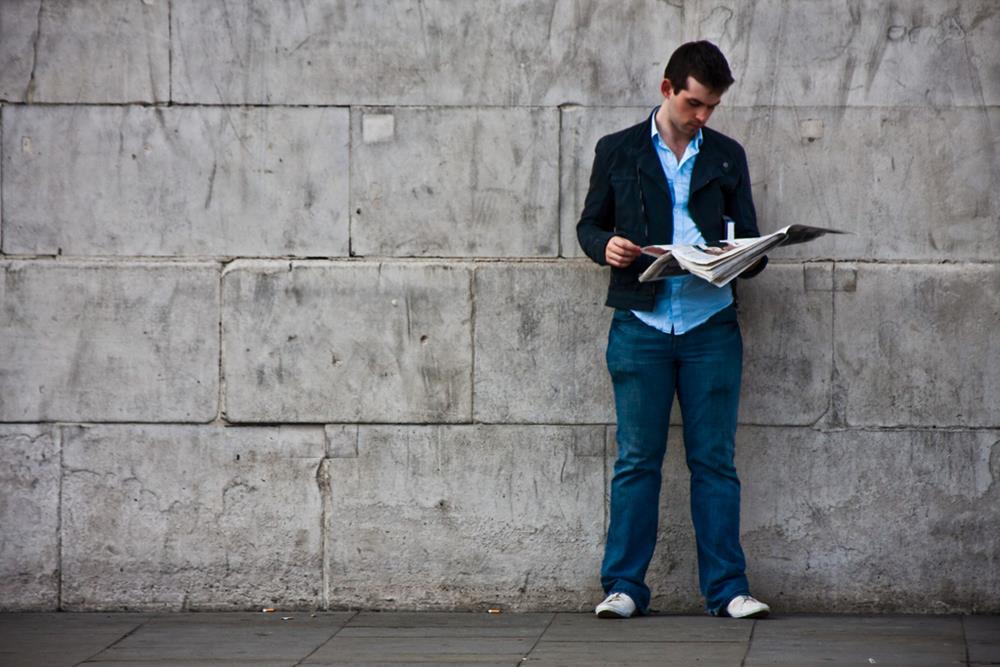 Guy standing and reading a newspaper, Spotlight Europe